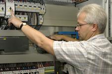 Elektrotechniker bei Elektromontage im Schaltschrank einer Absauganlage